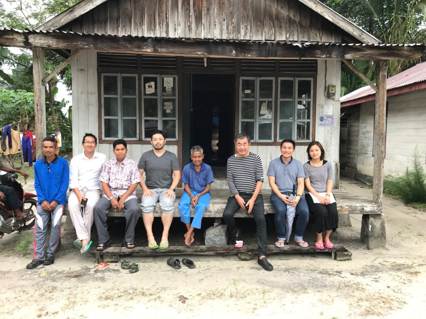 foto bersama di depan rumah tradisional penduduk